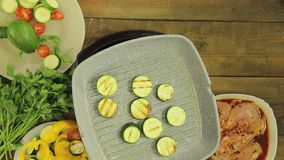 Green courgettes are fried in butter in a grill pan for garnish to the chicken. Close-up stock video footage