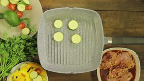 Green courgettes are fried in butter in a grill pan for garnish to the chicken. Close-up stock footage