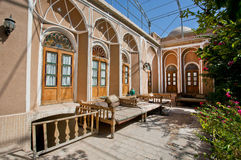 Green courtyard of beautiful iranian mansion with Ottoman beds Royalty Free Stock Images