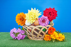 On the green cover of a basket with Easter eggs and different colors Royalty Free Stock Photos