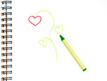Green crayon on sketch paper with a doodle of a pl Stock Image