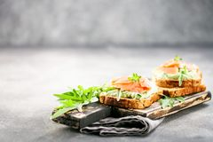 Green cream cheese, salmon and arugula sandwich. On a wooden board. Smorrebrod stock photography