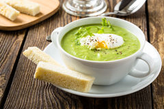 Green cream soup with poached egg. And croutons Royalty Free Stock Photo