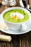 Green cream soup with poached egg. And croutons Stock Photo