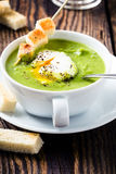 Green cream soup with poached egg Stock Photo