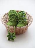 Green crochet baby booties with head band,  in bascket Royalty Free Stock Photography