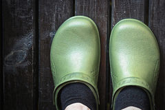 Green crocs clog worn by the man in black socks. On terrace Royalty Free Stock Photo