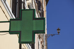 Green cross neon sign outside pharmacy. Stock Photos