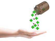 Green cross and pills falling Stock Photo