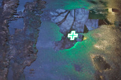 Green cross reflection in rain puddle. In dark urban evening Royalty Free Stock Photography