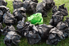 Green crumped paper between black paper balls on  grass field.jp Stock Images