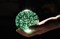 Green Crystal Ball on Hand Stock Image