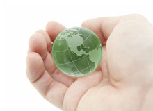 Green crystal globe in hand Royalty Free Stock Image
