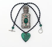 Green crystal necklace & perfume bottle isolated Stock Photos