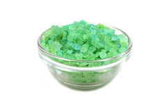 Green crystals of sea salt in a glass container. On a white background Stock Photos