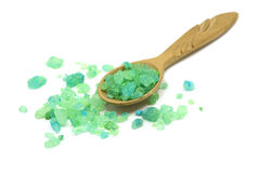 Green crystals of sea salt in a wooden spoon. On a white background Royalty Free Stock Image