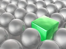 Green cube and grey spheres Royalty Free Stock Image
