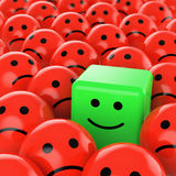 Green cube smiley happy. A green happy cube smiley between many red spherical sad others as concept for unique, optimistic, positive, difference Royalty Free Stock Photography