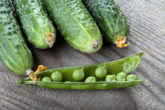 Green cucumbers and peas pod on a table Stock Photos