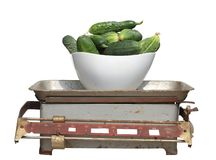 Green cucumbers in a white cup on old mechanical scales isolated Royalty Free Stock Photos