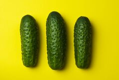 Green cucumbers on yellow Royalty Free Stock Image