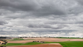 Green cultivated fields against cloudy stormy sky Stock Photo