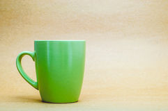 Green Cup On Brown Eco Background. Green Nature Cup Of Coffee On Plain Eco Brown Background, Safe Nature Concept Royalty Free Stock Photography