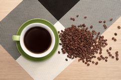 Cup of coffee on the table background and tablecloth and scattered coffee beans. Green cup of coffee on the background of the pink wood table and black and Royalty Free Stock Images