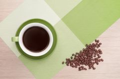 Green cup of coffee on the table background and tablecloth and beans. Green cup of coffee on the background of the pink wood table and tablecloth and beans. View Royalty Free Stock Photography