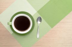Green cup of coffee on the table background and tablecloth and and spoon. Green cup of coffee on the background of the pink wood table and tablecloth and and Royalty Free Stock Photo