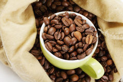 Green cup in coffee bag Royalty Free Stock Images