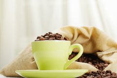 Green cup with coffee beans against bag. Green cup with coffee beans against textile bag Royalty Free Stock Images