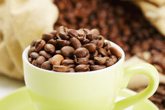 Green cup with coffee beans closeup Stock Photography