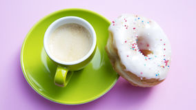 Green cup of coffee with donut on pink table stock images
