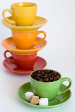 Green cup with coffee grains and sugar compared to other bright Royalty Free Stock Image