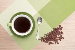 Green cup of coffee on the table background and tablecloth and beans and spoon. Green cup of coffee on the background of the pink wood table and tablecloth and Royalty Free Stock Image