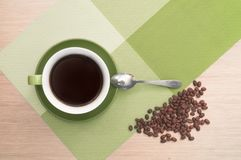 Green cup of coffee on the table background and tablecloth, beans and spoon. Green cup of coffee on the background of the pink wood table and tablecloth and Stock Photography