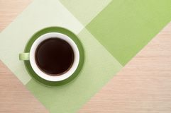 Green cup of coffee on the table background and tablecloth. Green cup of coffee on the background of the pink wood table and tablecloth. View from top Stock Images