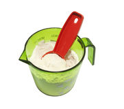 Green cup with flour and spoon Stock Photos