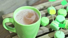 Green cup of the hot chocolate and green macaroons stock video footage
