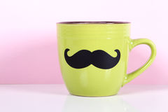 Green cup with paper mustache o Royalty Free Stock Photography