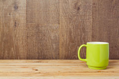 Green cup on rustic table over wooden background Stock Images