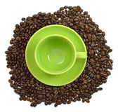 Green cup and saucer in the coffee beans Royalty Free Stock Photos