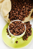 Green cup and saucer with coffee crop Stock Photos