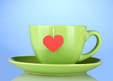 Green cup with saucer and tea