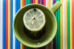 Green cup of tea with lemon. On a bright colored striped background Stock Photography