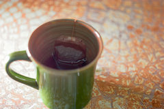 Green cup of tea with teabag on table with copy space, selective focus Stock Photo