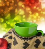 Green cup, warm scraf with heart pattern and festive glitter chr. Istmas decoration ball stock photography