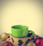 Green cup, warm scraf with heart pattern and festive glitter chr. Istmas decoration ball (Filtered image processed vintage effect royalty free stock photo