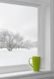 Green cup on a windowsill. With winter landscape seen through the window royalty free stock photography